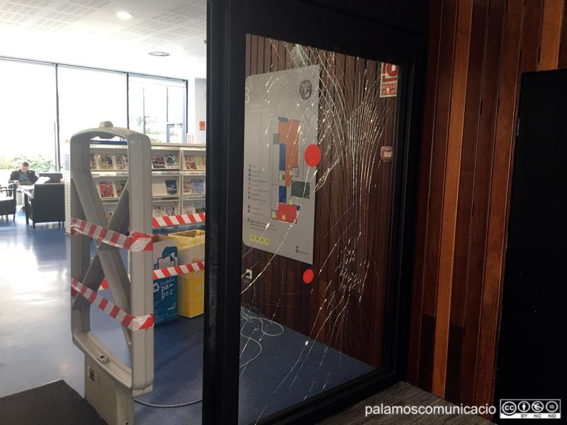 Vidre lateral de la porta d'accés a la biblioteca trencat.