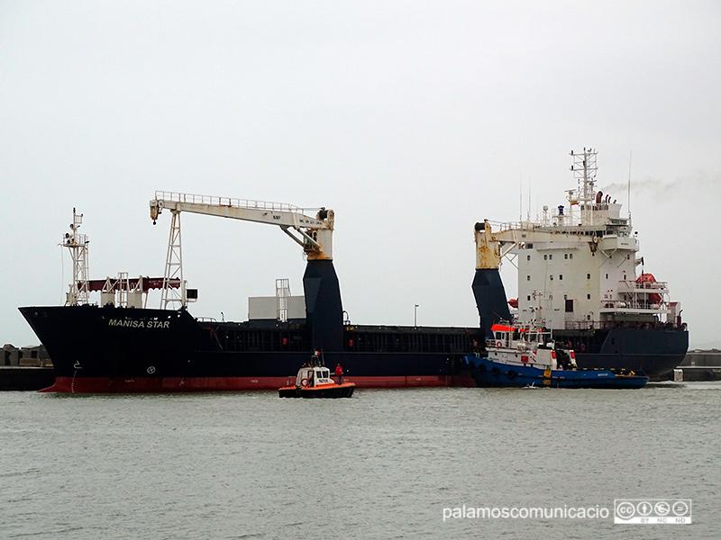 El mercant Marisa Star té trencades les amarres i un remolcador l'empeny contra el dic del port.
