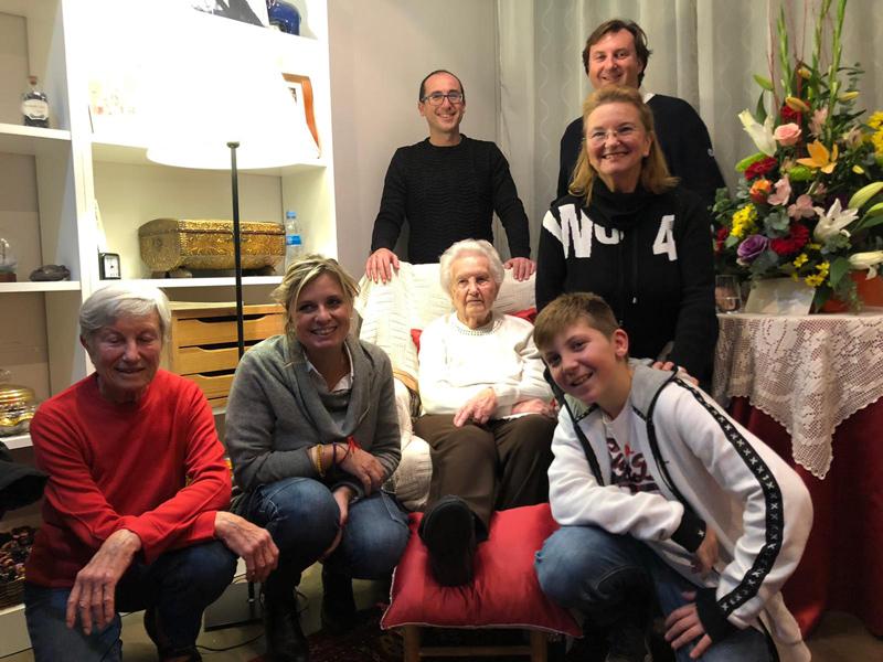 La senyora Dolors Puig acompanyada de l'alcalde i la regidora de Gent Gran i d'una part de la seva família. (Foto: Ajuntament de Palamós).