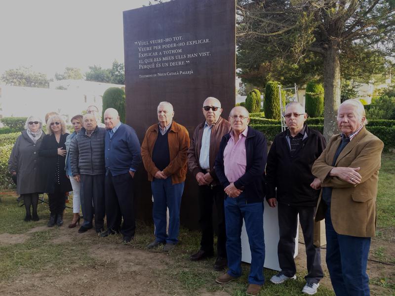 Familiars dels nou veïns del municipi que varen ser deportats, davant l'escultura dedicada a la seva memòria, al cementiri de Sant Joan. (Foto: Ajunta