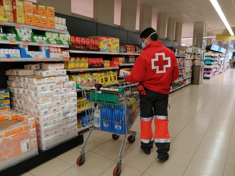 Personal de Creu Roja comprant material al supermercat que després portarà a domicili. (Foto: Creu Roja Palamós).