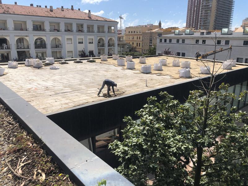 Operaris de la brigada treballant damunt la coberta de la Biblioteca Municipal. (Foto: Ajuntament de Palamós).