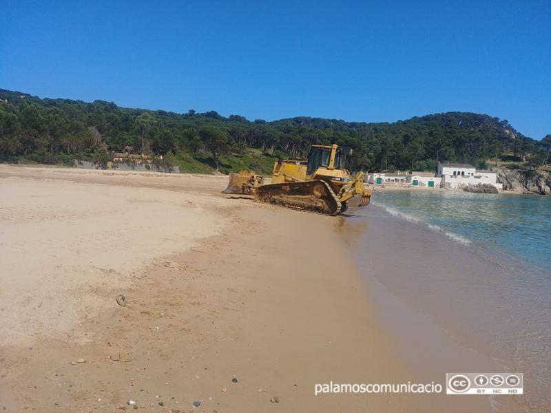 Excavadora aplanant la platja de Castell.