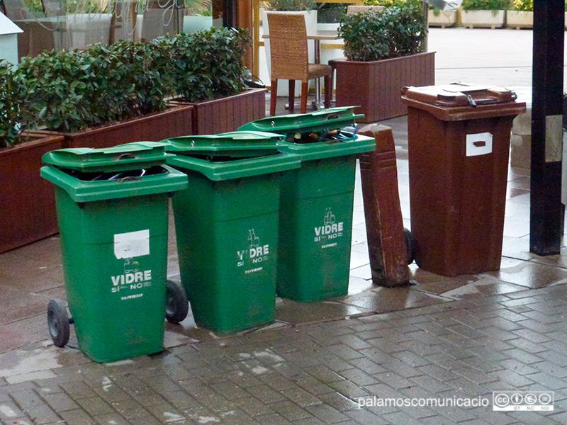 Contenidors de reciclatge a la porta d'un establiment de Palamós.