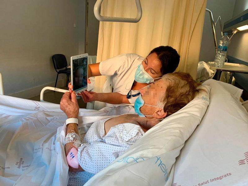 Una voluntària ajuda a una persona ingressada a fer una videoconferència. (Foto:  SSIBE).