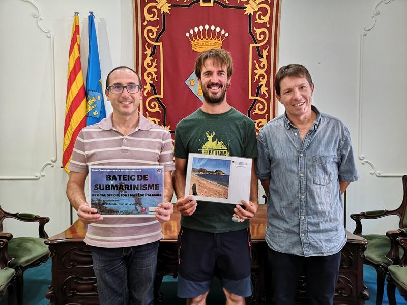 Pau Fernández, guanyador del concurs, entre l'alcalde Lluís Puig i el regidor Xavier Lloveras. (Foto: Ajuntament de Palamós).