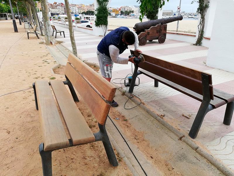 Un operari realitzant les feines de polit dels bancs del passeig. (Foto: Ajuntament de Palamós).