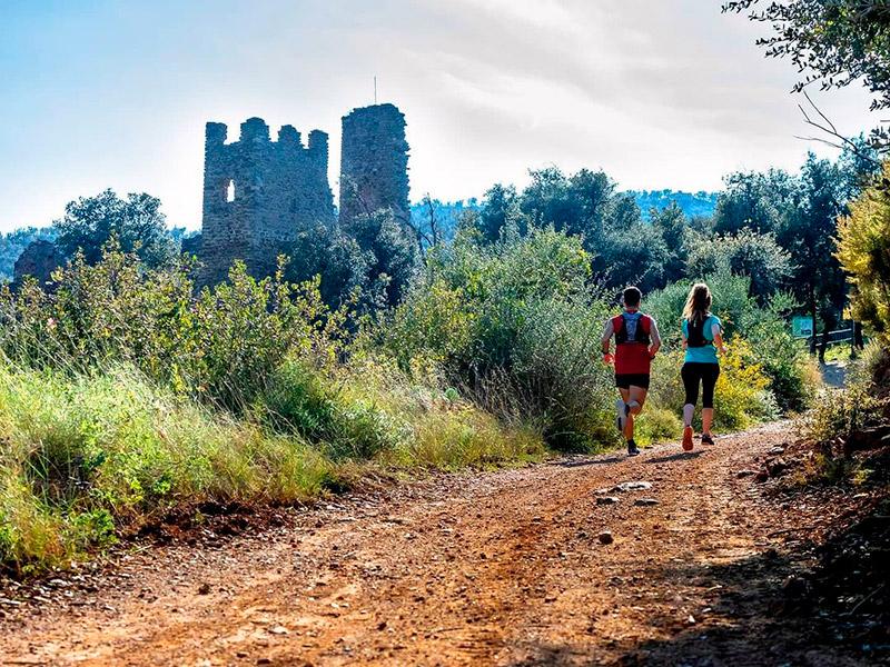 Dues persones fent esport a tocar del Castell de Vila-romà. (Foto: Deparament d'Esports de l'Ajuntament de Palamós).