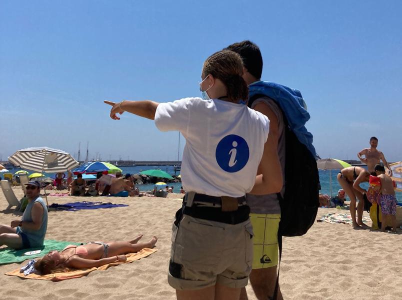 Una de les informadores realitzant la seva tasca a la platja Gran. (Foto: Ajuntament de Palamós).