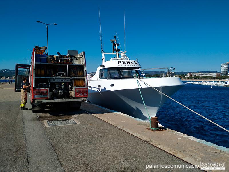 La barca amarrada a port, custodiada per una unitat dels Bombers de la Generalitat.